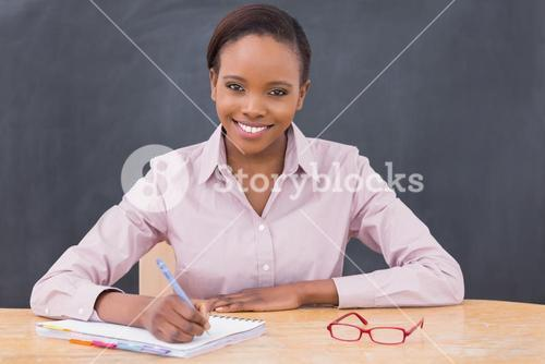Smiling teacher writing