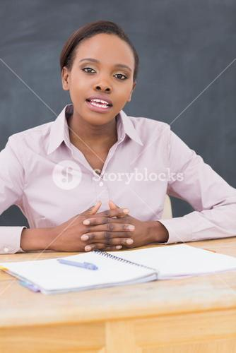 Teacher sitting at desk while speaking
