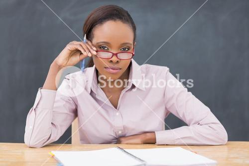 Serious teacher sitting at desk while touching her glasses