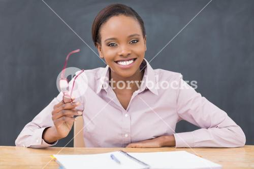 Teacher sitting at desk while holding glasses