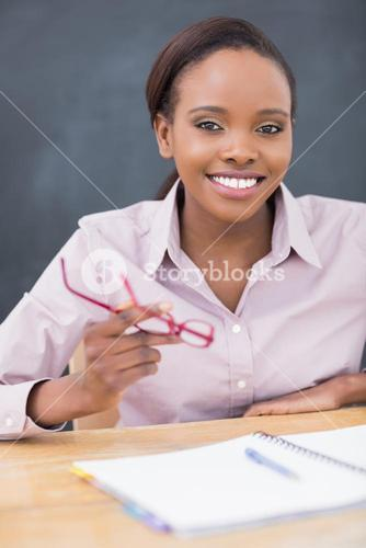 Teacher holding glasses while smiling