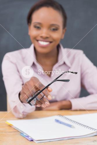 Focus on glasses of a teacher sitting at desk
