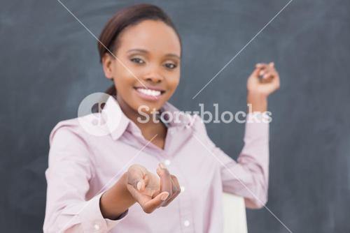 Black teacher showing the blackboard while smiling