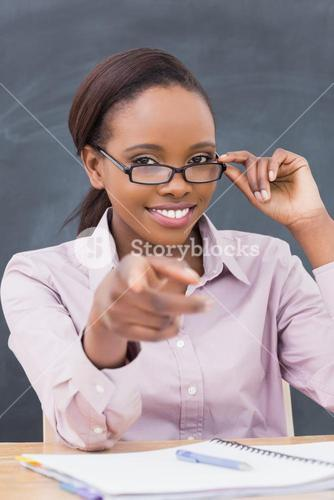 Teacher touching her glasses while sitting at desk