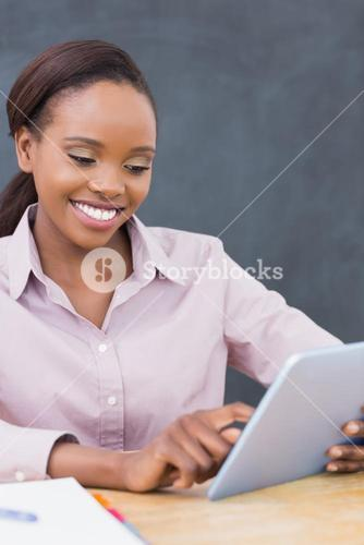 Teacher smiling while using a tablet computer