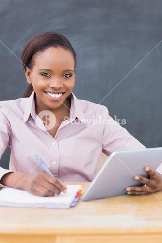 Teacher writing while using a tablet computer