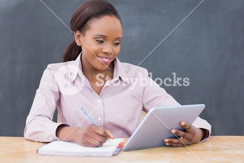 Teacher writing while looking at a tablet computer