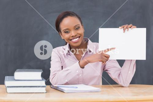 Black teacher holding a blank paper while smiling