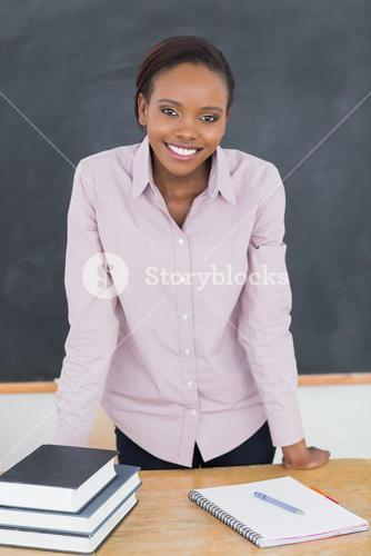 Teacher standing up while leaning on desk