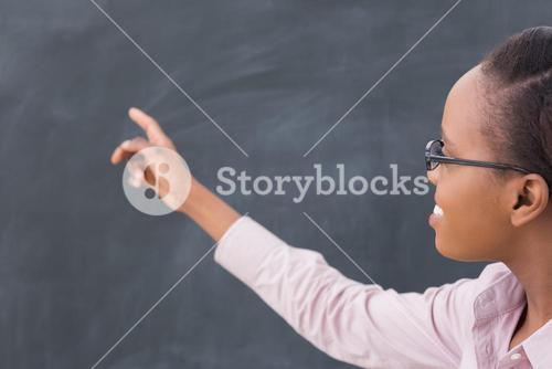 Black teacher pointing the blackboard