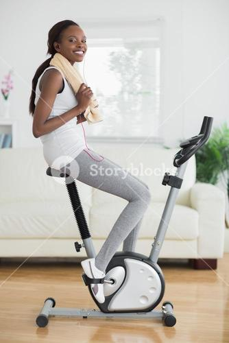 Black woman on an exercise bike smiling