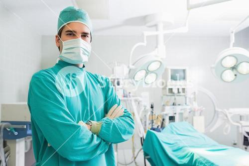 Serious surgeon standing with arms crossed