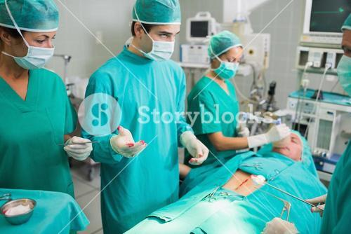 Surgeons standing next to a patient
