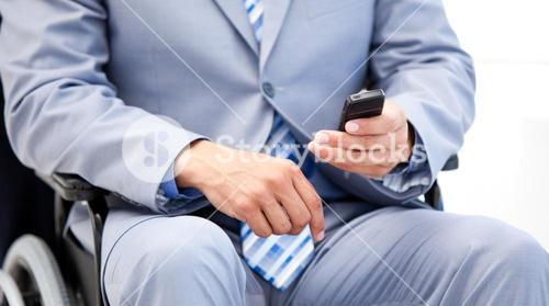 Close up of a businessman sitting on a wheelchair sending a text