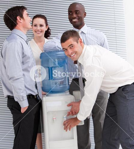 Confident business people interacting at a watercooler