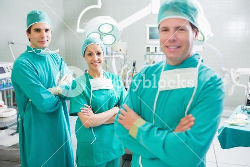 Smiling surgeons looking at camera with crossed arms