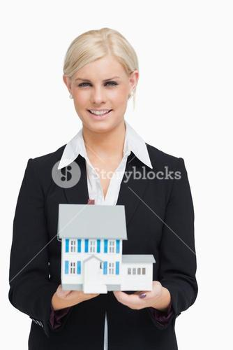 Smiling real estate agent holding a model house