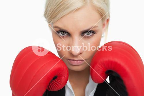 Serious green eyed woman with red gloves fighting
