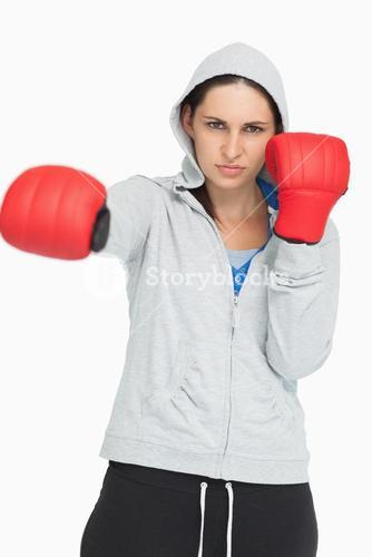 Brown haired woman in sweatshirt boxing