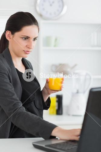 Woman using a laptop while holding a juice glass