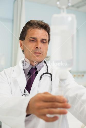 Thoughtful doctor in a hospital adjusting IV