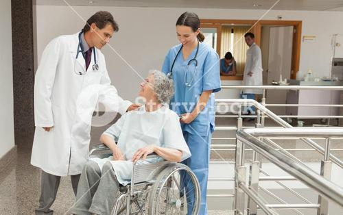 Nurse and doctor talking with old woman in wheelchair