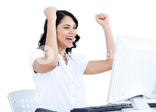 Happy businesswoman punching the air in front of her computer