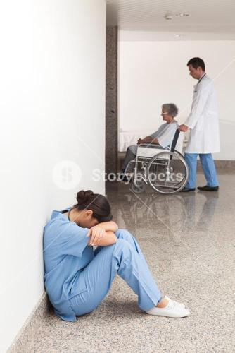 Nurse sitting on the ground with head in hands