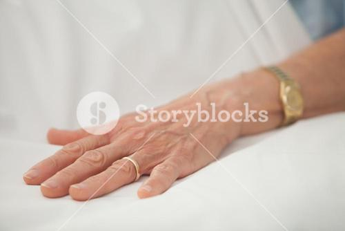 Hand of old woman with golden jewellery