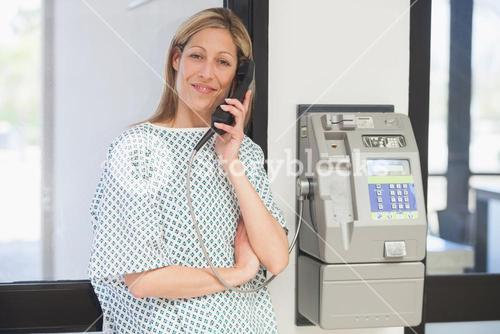 Smiling patient using payphone