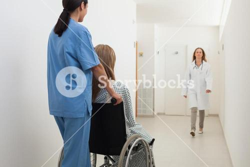 Nurse pushing patient in wheelchair with doctor approaching