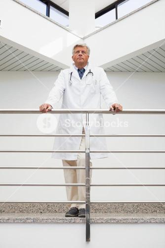 Thinking doctor stands at railing