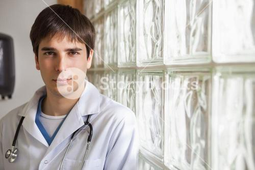 Doctor leans against glass wall