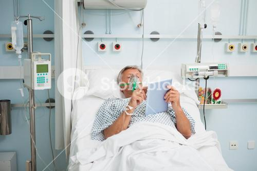 Patient lying in bed wearing oxygen mask