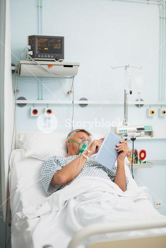 Man in oxygen mask reading in bed