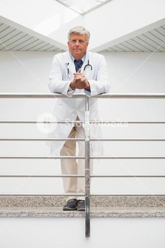 Doctor leaning on rail in hospital corridor