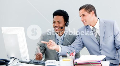 Handsome businessman pointing at the screen to show the results to his partner