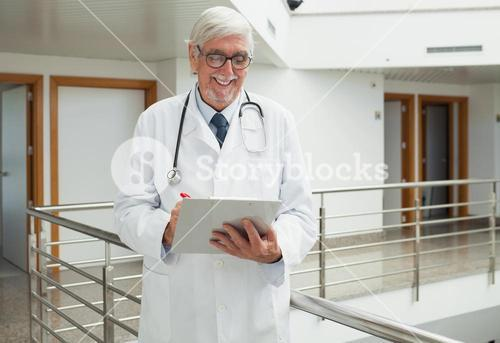 Doctor smiling as looks at patient file