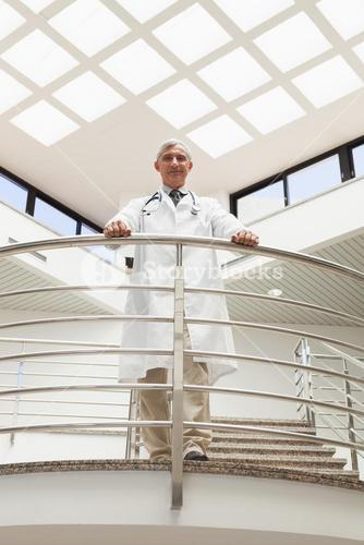 Doctor standing an the railing at the corridor looking down