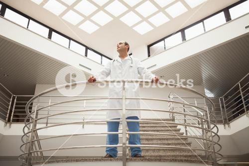 Doctor standing in stairwell looking around