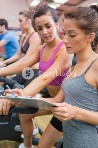 Gym Instructor helping woman on exercise bicycle