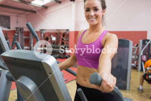 Smiling brunette stepping on a step machine
