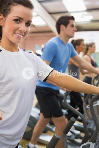 Smiling woman with other people stepping on step machines