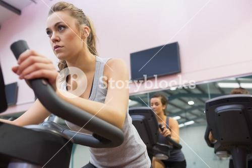 Woman training on exercise bike in a spinning class
