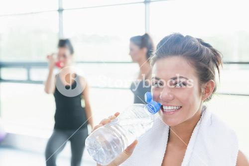 Women talking while another drinking water in fitness studio