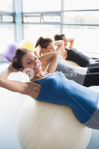 Smiling women doing situps