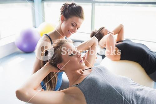 Female trainer helping woman doing situps