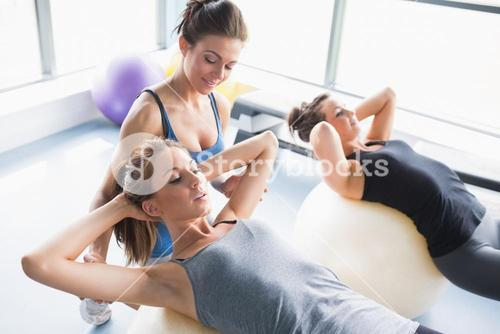 Female trainer teaching women doing situps