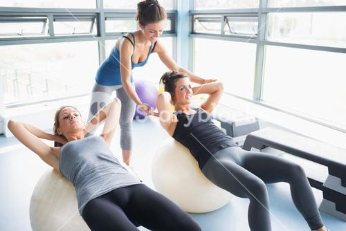 Women doing situps on exercise balls in gym