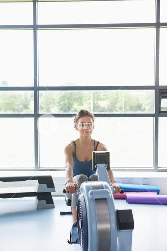 Woman training on row machine